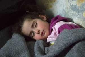 Rifaat's daughter sleeps in the corner of their apartment. The family's full names are not being used for security reasons. (Doug Hostetter/MCC)
