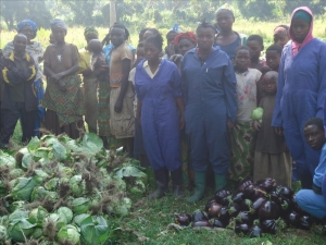 Residents of the Mubimbi IDP camp near Minova, DR Congo, are pictured with a pile of eggplant and a pile of cabbages that were harvested from their community garden. ECC Photo/Patrick Bulonza