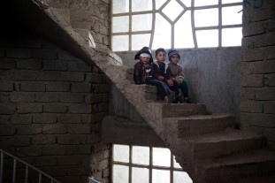 Khaled (3), Sahram (6) and Shawesh (8) sit on steps in the unfinished house their families are taking refuge in. The family is receiving food assistance through an MCC-supported project in northern Iraq. Last names are withheld for security reasons. (MCC photo/staff)